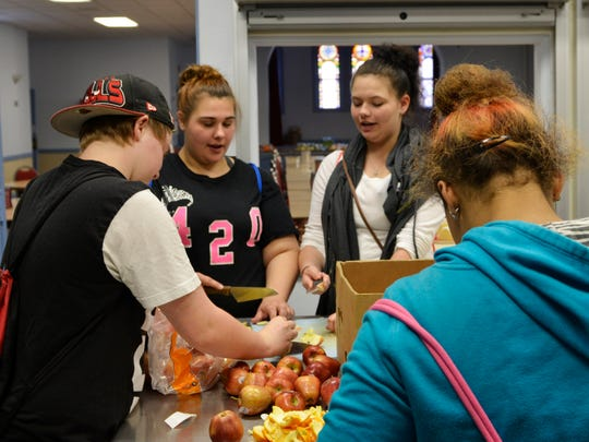 Wilson Junior High and Lincoln High School students Faith Ladue, Taylor Naidl, Mackenzie Busalacchi and Summer Sprang cut apples at First Presbyterian Church in Manitowoc on Wednesday, May 25. Ladue, Naidl and Sprang volunteer each week as part of the Restorative Justice program, and brought along Busalacchi for fun and companionship. The four helped to prepare dinner and then stayed and ate together.