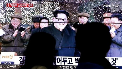 People walk by a TV news program showing North Korean leader Kim Jong Un in Seoul, South Korea, Friday, March 4, 2016. Kim ordered his military on standby for nuclear strikes at any time, state media reported Friday, an escalation in rhetoric targeting rivals Seoul and Washington that may not yet reflect the country's actual nuclear capacity. (AP Photo/Ahn Young-joon)