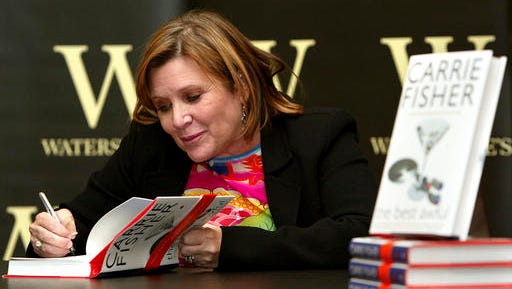 "FILE - In this Friday, Feb. 20, 2004 file photo, author Carrie Fisher autographs her new book ""The Best Awful"" at a promotional event in London. On Tuesday, Dec. 27, 2016, a publicist said Fisher has died at the age of 60."