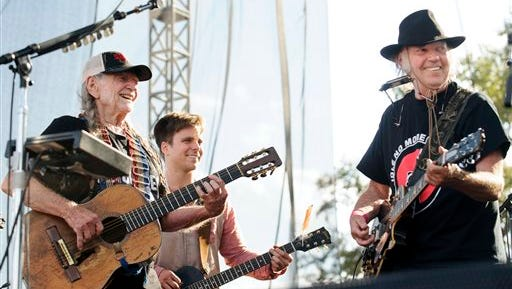 """Willie Nelson, his son Lukas Nelson and Neil Young perform the folk song """"This Land is Your Land"""" during the Bold Nebraska Harvest of Hope concert on Saturday, Sept. 27, 2014, at Art & Helen Tanderup's farm north of Neligh, Neb."""