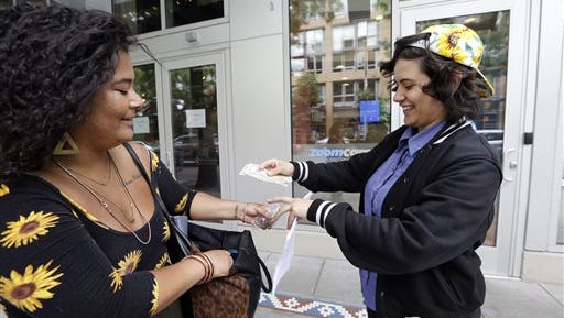 """Yeni Sleidi, known as the """"weed fairy,"""" right, buys marijuana from a dealer, who declined to be identified, in Seattle?s Capitol Hill neighborhood Wednesday, May 28, 2014, where this past weekend Sleidi posted 50 fliers with nuggets of marijuana taped to them. Sleidi, a 23-year-old who works in social media, has been visiting Seattle from New York where last year she did a similar posting, albeit anonymously."""