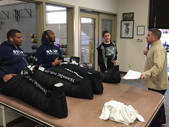 """Sports agent Andrew """"Buddy"""" Baker talks with Deon Simon, left, and Obum Gwacham at St. Vincent Sports Performance in Indianapolis. They're wearing compression boots to promote muscle recovery. Baker's son Braden is also in the photo."""
