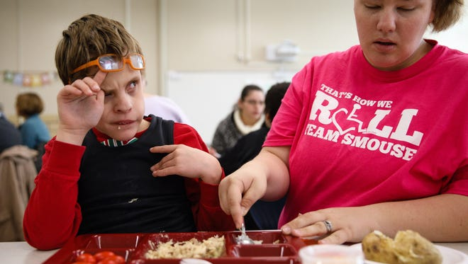 Evan Ames, 11, eyes associate Megan Clark as she cuts up his food Monday, Nov. 21, 2016, during the Thanksgiving Feast at Smouse Opportunity School in Des Moines.