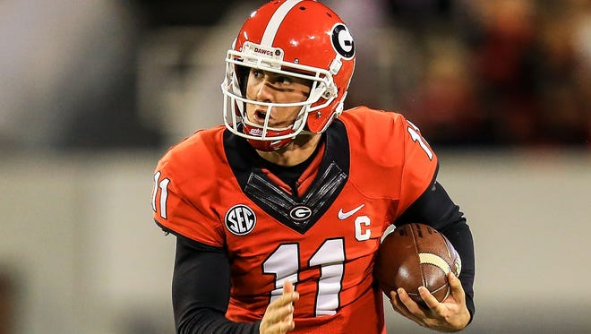 Former Georgia Bulldogs quarterback Aaron Murray (11) runs the ball in the first half against the Kentucky Wildcats at Sanford Stadium in Athens, Ga. on Nov. 23, 2013.