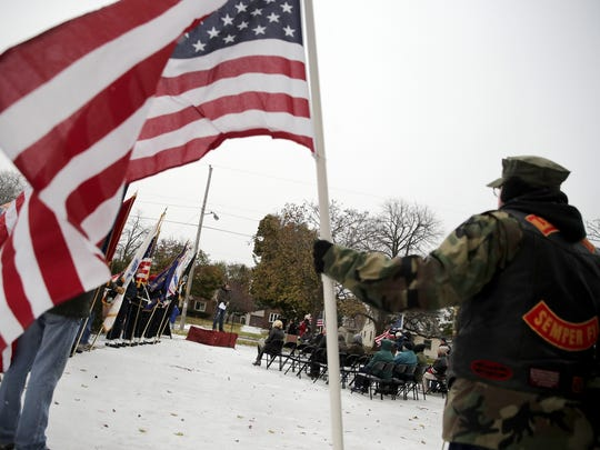 "A veteran looks on while holding an American flag while Alex Schultz, Sculpture Valley president, speaks during the rededication and commemoration of ""The Spirit of the American Doughboy"" statue Saturday in Appleton."