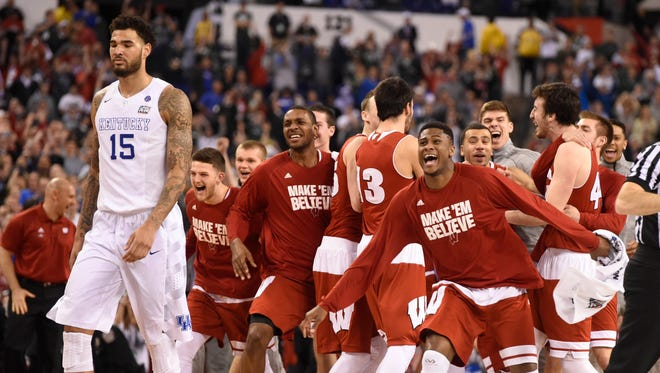 Wisconsin Badgers celebrate as Kentucky Wildcats forward Willie Cauley-Stein (15) walks off the court as they upset Kentucky 71-64 in the 2015 NCAA Men's Division I Championship semi-final game at Lucas Oil Stadium.