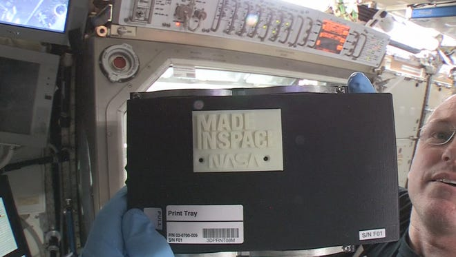 """In 2014, International Space Station Commander Barry """"Butch"""" Wilmore holds up the first object made in space with additive manufacturing, or 3-D printing. Wilmore installed the printer developed by engineers from Made In Space and NASA on Nov. 17, 2014, and helped crews on the ground with the first print on Nov. 25, 2014."""