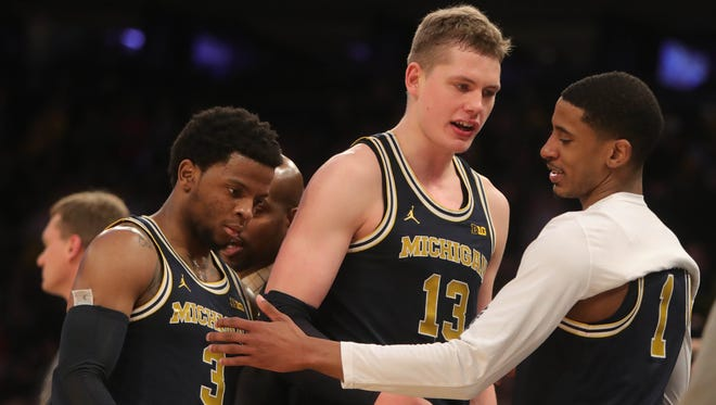 Michigan players Zavier Simpson, Moritz Wagner and Charles Matthews on the bench during the final seconds against Nebraska Friday, March 2, 2018 at Madison Square Garden in New York.