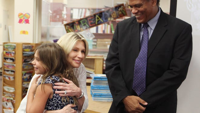 Emily Bonetti, of Three Oaks Elementary School, hugs Lucy Davis, of BB&T Bank, after receiving a certificate for completing the requirements of the Self-Reliance Club on Tuesday. Vasquez has earned a savings bond in the amount of $25 through BB&T Bank.