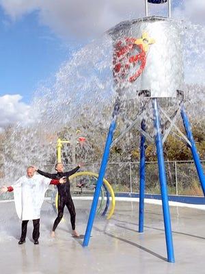 Village of Santa Clara Mayor Richard Bauch (white) tries the new Splash Park in Santa Clara during a ribbon cutting ceremony.