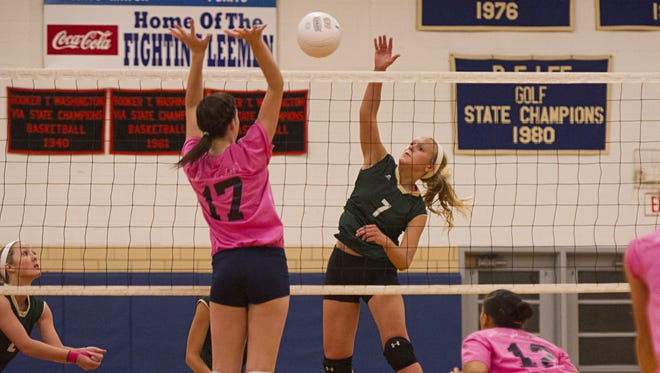 Wilson Memorial's Jordan Poole, center, tries to make a return past a leaping Alyx Steitz of Robert E. Lee during their volleyball game on Oct. 13, 2014.