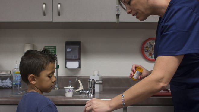 School nurse Jennifer Costello gives a student his medication in the nurses office at Webster Elementary School.