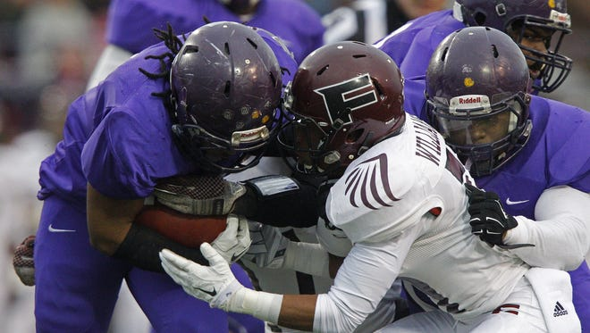 Memphis Trezevant's Cordarrian Richardson, left, is hit by Fulton's Ethan Williams in the Division I Class 4A Tennessee high school football championship game Dec. 6, 2014, in Cookeville, Tenn.