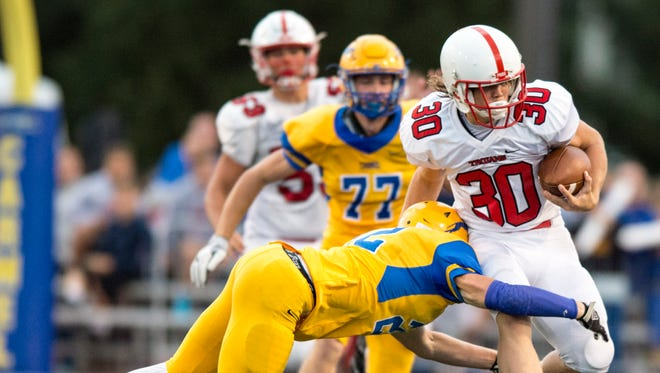 Center Grove High School freshman Carson Steele (30) rushes the ball upfield and is hit by Carmel High School junior Nate Frey (22) during the first half of an IHSAA high school football game at Carmel High School, Friday, September 1, 2017.