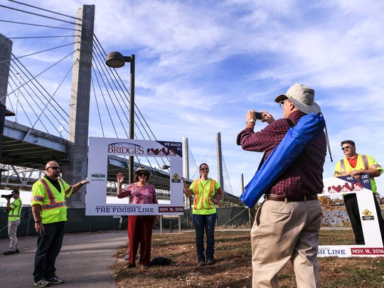"""Mary Kramer waves to husband Carl Kramer as he takes a picture of her before the official celebration of the completion of the downtown crossing portion of the Ohio River Bridges Project Friday afternoon. Kramer served on the Ohio River Major Investment Study committee, which recommended the Ohio River Bridges Project, including the two new bridges that link Southern Indiana to Louisville as well as the reconstruction of """"Spaghetti Junction."""""""
