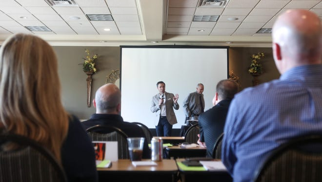 Guest speaker and real estate agent Tyler Minges talks to a room of Huff Realty agents during a work training event on Monday, May 21, 2018, at Devou Park in Covington, Kentucky.