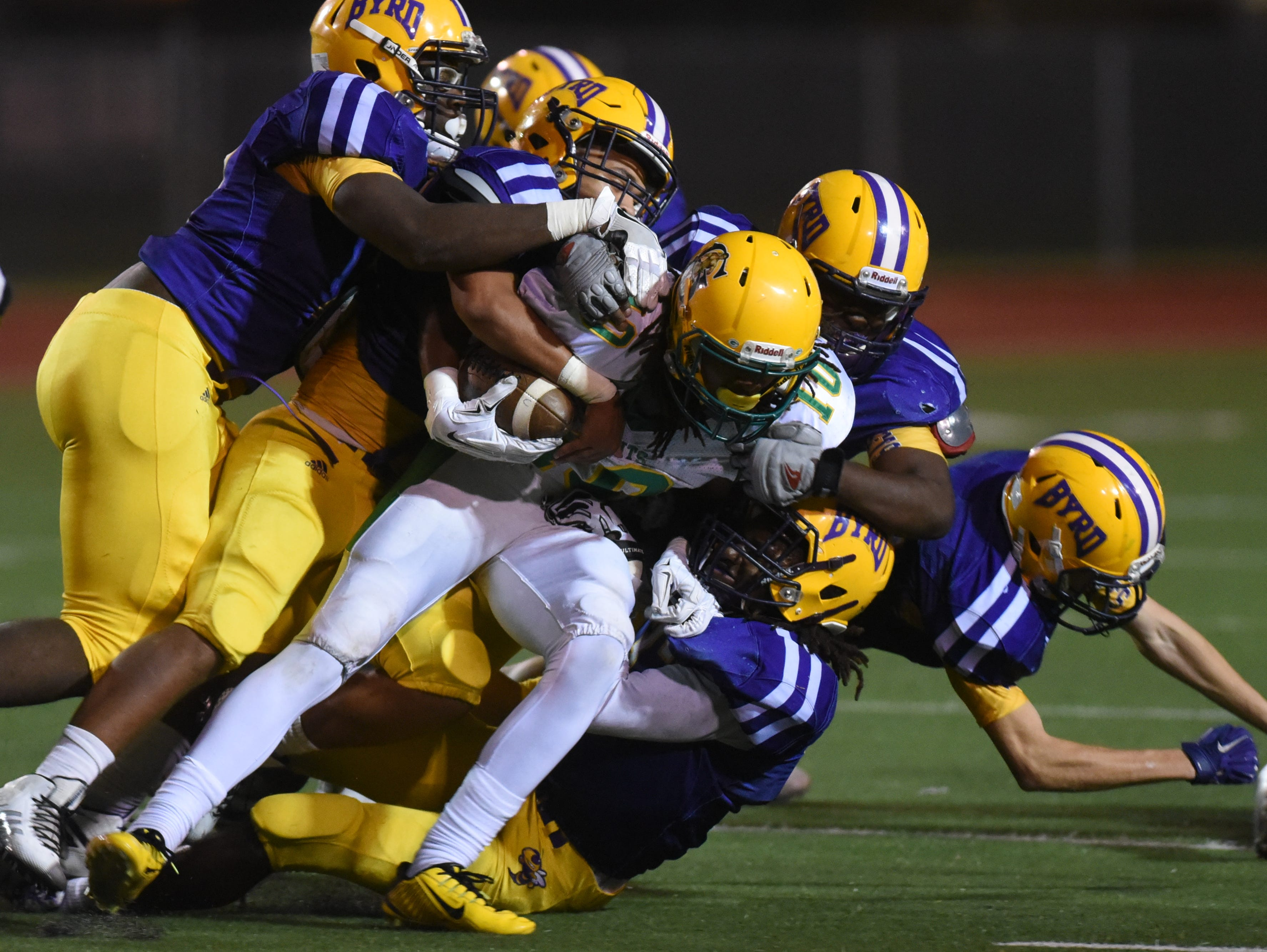 Green Oaks Kenric Jackson is swarmed by the Yellow Jackets defensive line during their game at Lee Hedges Stadium.