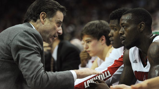 Louisville head coach Rick Pitino (left) talks with Chris Jones on the bench as the Cardinals take on FIU on Dec. 5 at the KFC Yum! Center. UofL won 82-57.