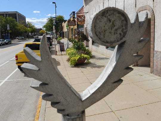 Broadway District stores are set amid overflowing planters, eclectic sculptures and signs on Broadway in Green Bay October 2, 2015.