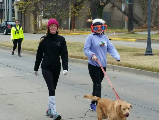Lori Wood and Dana Myers walk Biscuit the dog during
