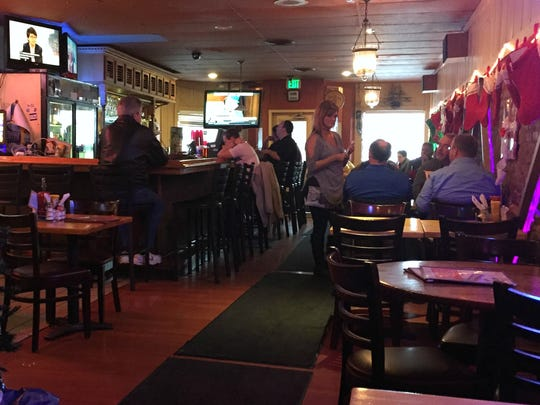 Bourbon Street Distillery manager Carrie Bowman takes orders from regulars getting their last tenderloin and pulled pork fixes at the Downtown Indy bar and restaurant. The place closes Jan. 6, 2017.
