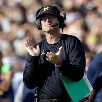 Michigan coach Jim Harbaugh claps after a touchdown