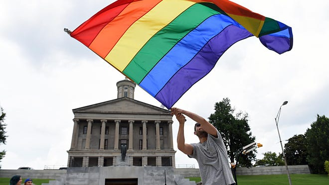 Christopher Shappley waves a gay pride flag during a celebration June 26 at Legislative Plaza after the Supreme Court officially recognized the legal authority for same-sex couples to be married.