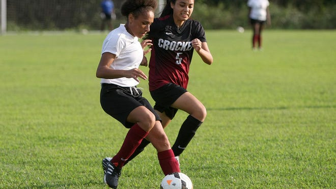 Liberty's Alyesia Pavia (7) works the ball against Crockett County's Gisselle Juarez (5) at Liberty on Thursday.