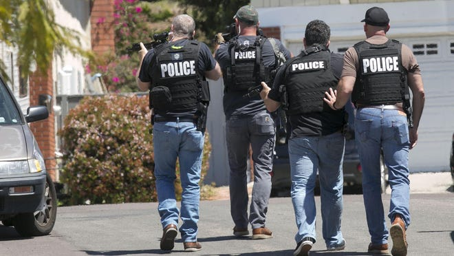 Heavily armed San Diego police officers approach a house thought to be the home of 19 year-old John T. Earnest, who is a suspect in the shooting of several people in a Poway synagogue, on Saturday, April 27, 2019, in San Diego, Calif.