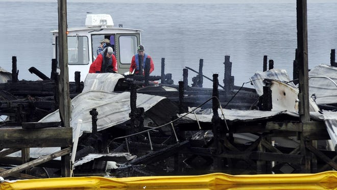 A crew looks at the charred remains of a boat following a fatal fire at a Tennessee River marina in Scottsboro, Ala., on Jan. 27.