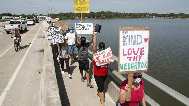 Protesters march across the Dunlawton Bridge in Port Orange on Sunday.