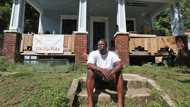 Terrence Langston, 37, sits on the front steps of a house Wednesday on East Voris Street in Akron. Langston, who runs his own construction company, is facing eviction from the home.