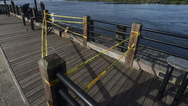 The railing and dock at the base of Market St. are damaged in Wilmington, N.C., Friday, August 28, 2020. According to a press release from the Wilmington Police Department, a vehicle went into the Cape Fear River around the base of Market St just after midnight. Authorities are working to recover the vehicle and any possible individuals inside.