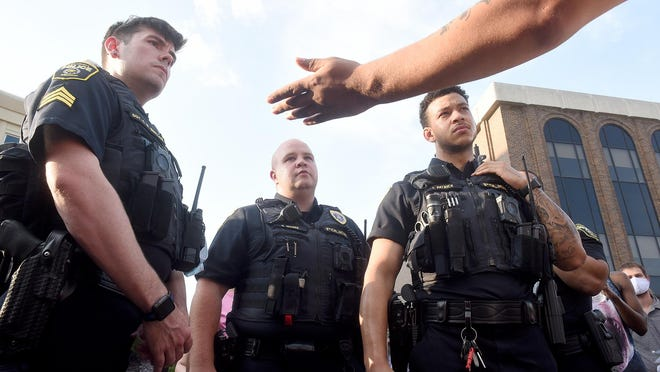 Columbia police officers listen to protesters' concerns during the protest Wednesday in the intersection in front of city hall. About 200 protesters marched downtown during the fourth night of protests for the killing of George Floyd by a police officer in Minneapolis.