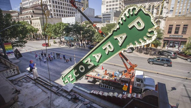 In 2015, construction workers block off Congress Avenue with an 80-foot crane while installing the Paramount Theatre's blade, which had been removed in 1964.