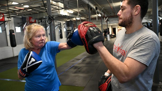 Before the Covid-19 pandemic hit, Kathleen Corcoran of West Roxbury threw a punch at Rafael Rivera, her boxing coach, during a Rock Steady boxing class for people with Parkinson's disease at the Nonantum Boxing Club in Newton. Corcoran was diagnosed in 2006.