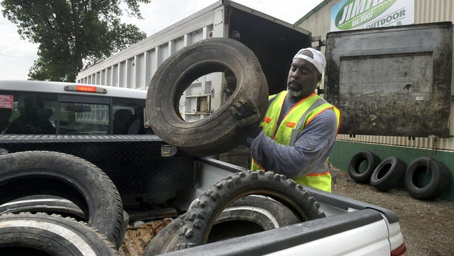 Damian Tracy, a JIMAX employee who volunteered to help out during the Tireless Project tire drop-off, transfers  tires into an awaiting semitrailer outside the JIMAX building in Peoria on Saturday morning.