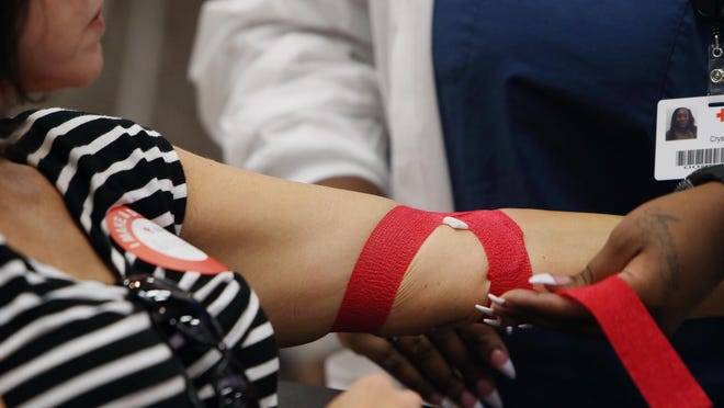 Crystal Poindexter, a collections technician with the American Red Cross of Birmingham, wraps tape around Allison Barker's arm during the Red Cross Blood Drive at the University of Alabama Ferguson Center ballroom on the UA campus in Tuscaloosa, Ala. on Tuesday Aug. 26, 2014.