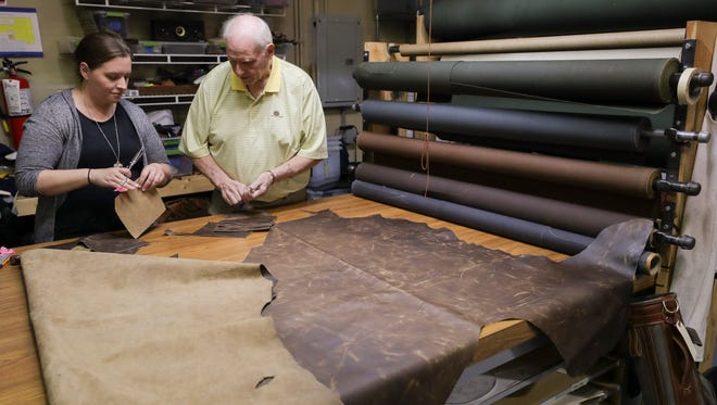 Meghan Leezer, left, and father Will Jacoby work on cutting leather at the Firbird Group shop.