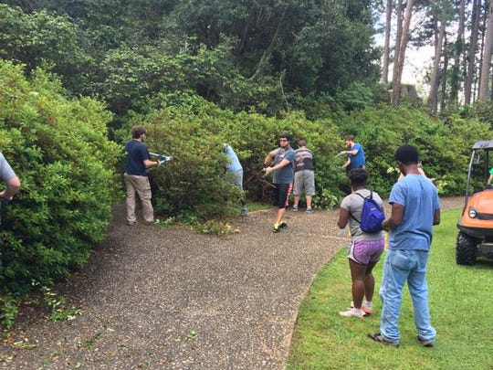 Students in the Chi Alpha Christian student organization at University of Louisiana at Lafayette and Nicholls State trim azalea bushes at Hodges Gardens State Park in Florien during spring break.