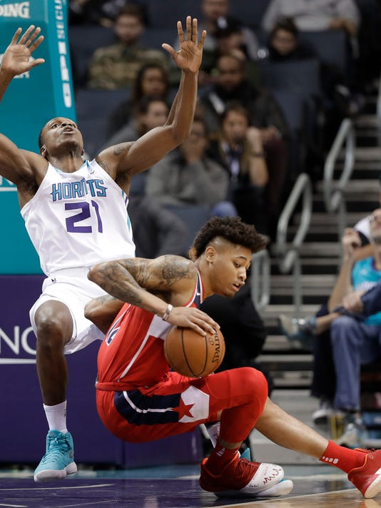Washington Wizards' Kelly Oubre Jr, front, knocks down Charlotte Hornets' Treveon Graham, back, during the first half of an NBA basketball game in Charlotte, N.C., Wednesday, Jan. 17, 2018. (AP Photo/Chuck Burton)