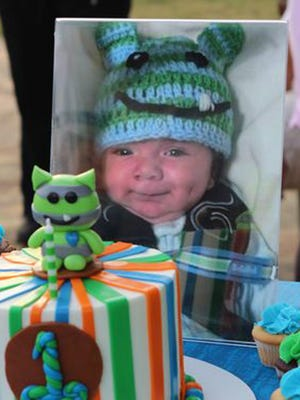 A photograph of Thomas Castellon II sits in front of his first birthday cake in September. A babysitter faces charges in his death at 2 months old.