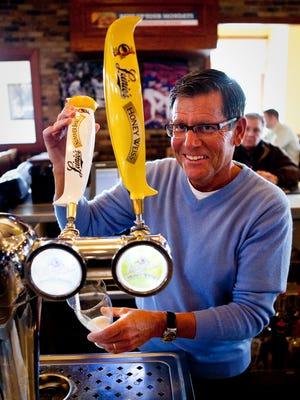 Jake Leinenkugel, former president of Jacob Leinenkugel Brewing Co. , pours a glass of Summer Shandy at Champps Restaurant in Brookfield in 2012.