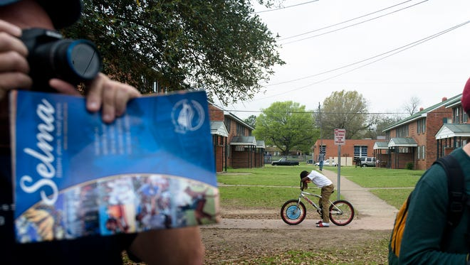 People photograph the National Parks Service 50th Anniversary Walking Classroom and March as a boy rests his head on his bike across the street from Brown Chapel AME Church in Selma, Ala., on Saturday, March 21, 2015.