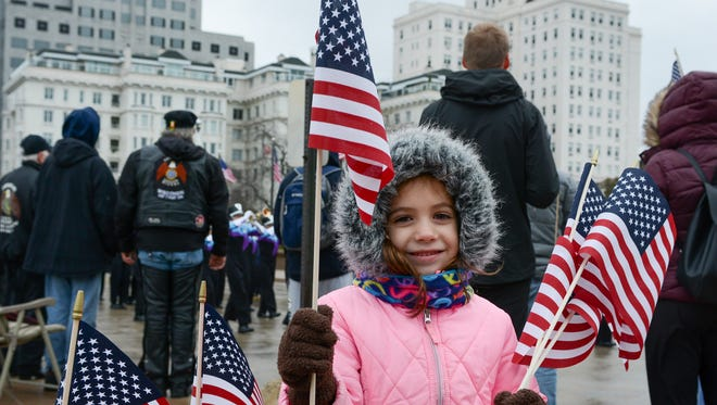 Arya Bernhardt, 5, of Watertown hands out flags in front of the Milwaukee County War Memorial Center near the end of the route for the 2017 Veterans Day Parade in downtown Milwaukee. The parade's 55th annual is this Saturday.