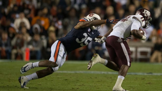Auburn defensive back Jermaine Whitehead (35) attempts to tackle Texas A&M wide receiver Malcome Kennedy (84) during the NCAA football game between Auburn and Texas A&M on Saturday, Nov. 8, 2014, in Auburn, Ala. Texas A&M defeated Auburn 41-28 after Auburn fumbled twice on there last two drives.