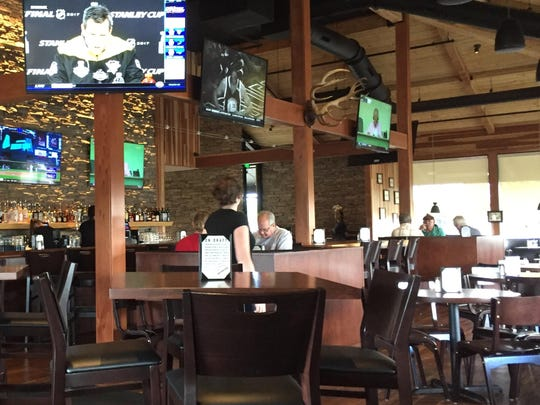 The interior of Redwood Rotisserie & Grill features a redwood ceiling, redwood accents and other natural materials.
