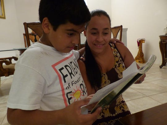 Leonardo Iriarte, left, and his mom, Yudit Savorit, look over a notebook that keeps tabs on everyone who's donated school supplies, toys and money.