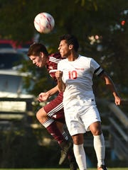 Ketcham's Daniel Veliz, right, heads the ball away from Arlington's Reed Burton, left, during Monday's game.