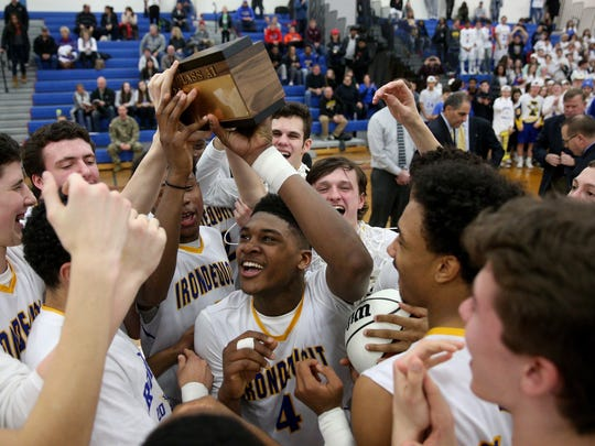 Irondequoit's Gerald Drumgoole (4) celebrates with teammates after the Eagles beat Athena 61-44 to win last season's Class A1 title.